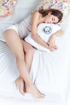 La jeune belle fille au lit avec le service d'horloge à la maison
