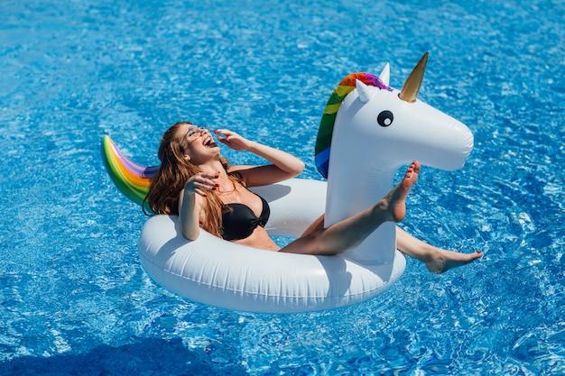Jeune belle fille aux cheveux bruns avec un bon bronzage figure dans la piscine sur une licorne gonflable en maillot de bain noir.