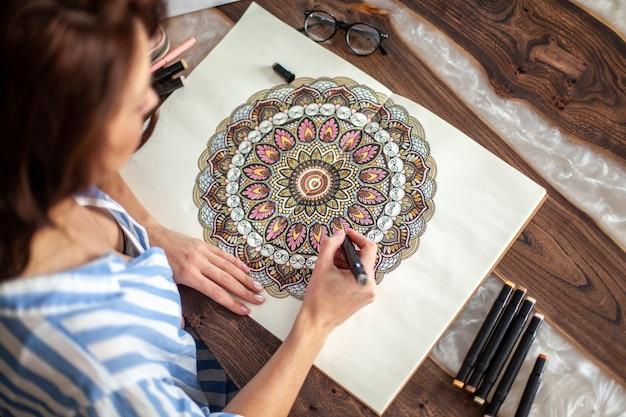 Jeune belle fille aux cheveux longs dessine un motif de mandala circulaire