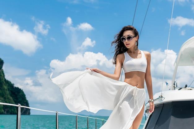 Jeune belle fille aux cheveux longs se tenant debout sur la proue du yacht