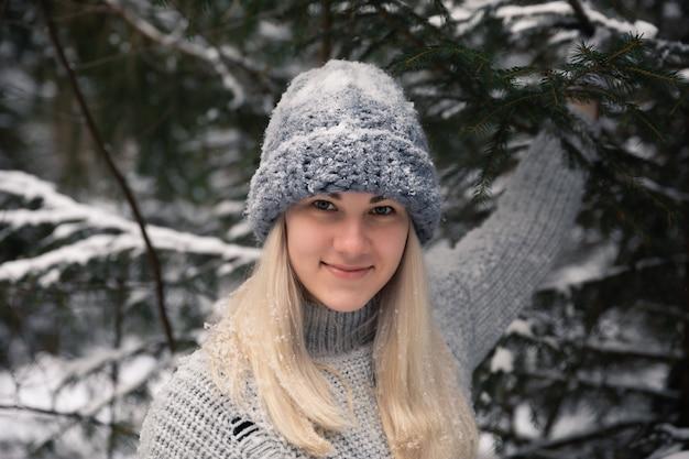 Jeune belle fille aux longs cheveux blancs joue des boules de neige. elle s'amuse, jette de la neige et se réjouit des chutes de neige. promenade d'hiver à l'extérieur.