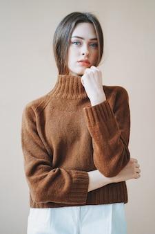 Jeune belle fille aux longs cheveux bruns aux yeux bleus en pull en tricot marron en regardant la caméra sur fond beige