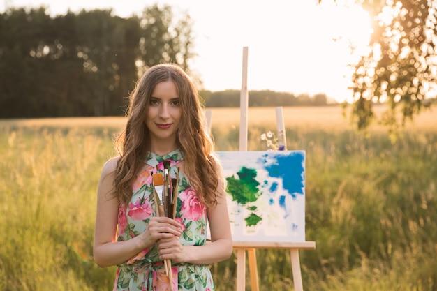 Jeune belle fille aux longs cheveux naturels dessine une image avec un chevalet dans la nature.