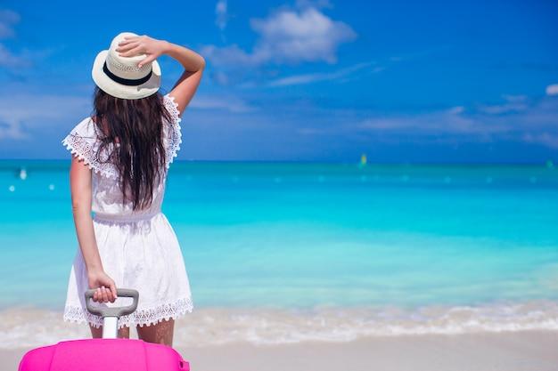 Jeune belle fille avec des bagages pendant les vacances à la plage