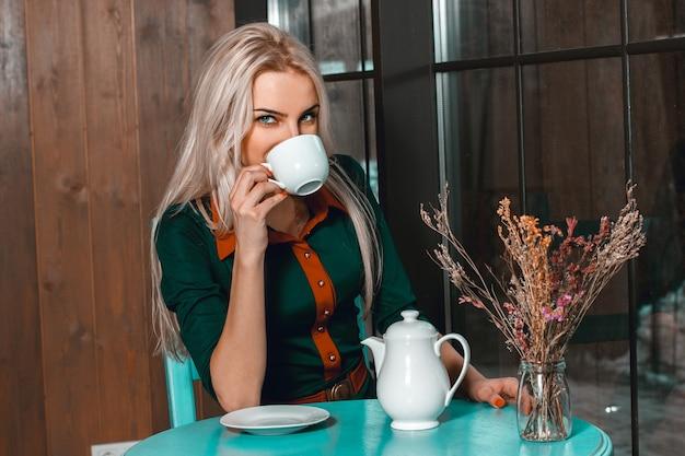 Jeune belle fille blonde boit du thé dans un café et regarde directement. belle fille au café avec une tasse de café.