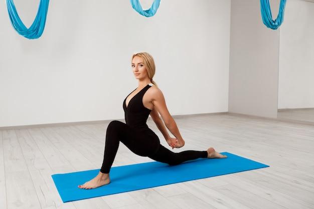Jeune belle fille blonde, pratiquer le yoga dans la salle de gym.