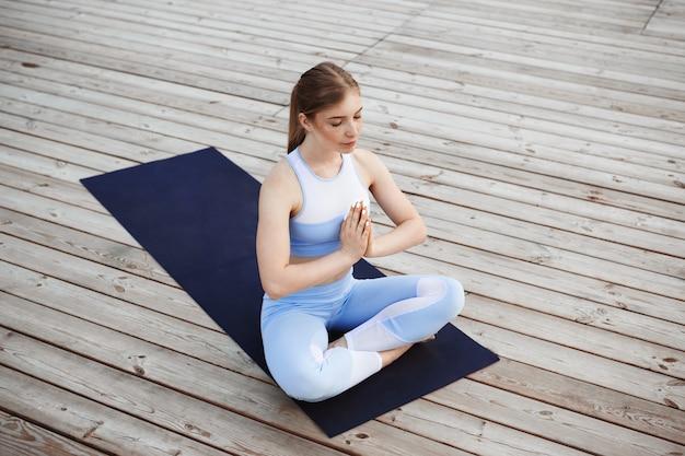Jeune belle fille blonde, pratiquer le yoga à l'extérieur.
