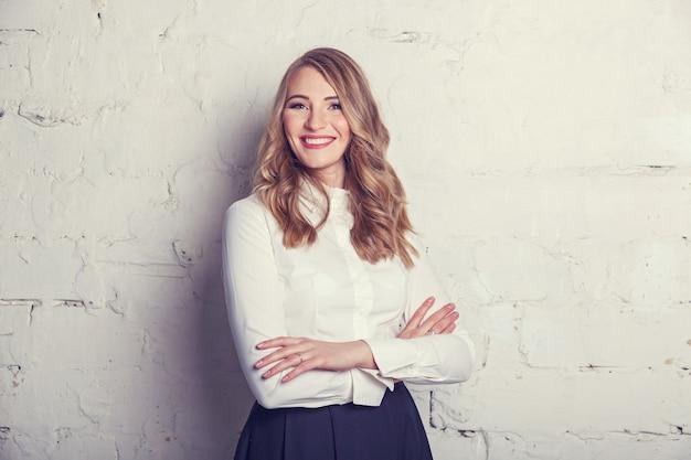 Jeune belle fille en blouse blanche et jupe noire en studio posant devant