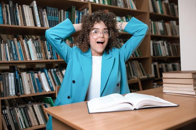 Jeune belle fille bouclée dans des verres et costume bleu assis avec des livres dans la bibliothèque.