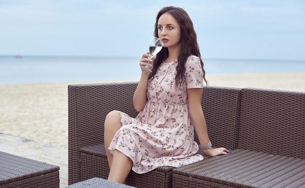 Jeune belle fille brillante dans une robe d'été assise sur la plage