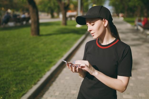 Jeune belle fille brune athlétique en uniforme noir et casquette utilisant un téléphone portable pendant l'entraînement, regardant sur un smartphone, debout sur le chemin dans le parc de la ville à l'extérieur