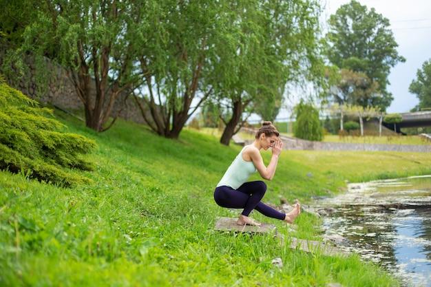 Jeune belle fille brune caucasienne faire du yoga sur une pelouse verte