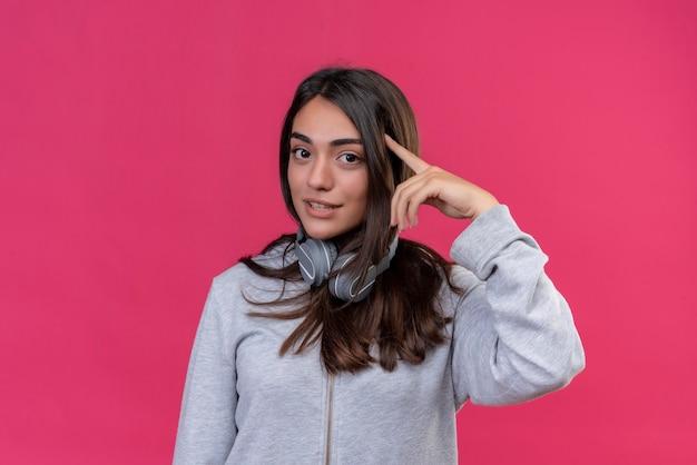 Jeune belle fille à capuche gris portant des écouteurs regardant la caméra toucher la tête avec le doigt debout sur fond rose