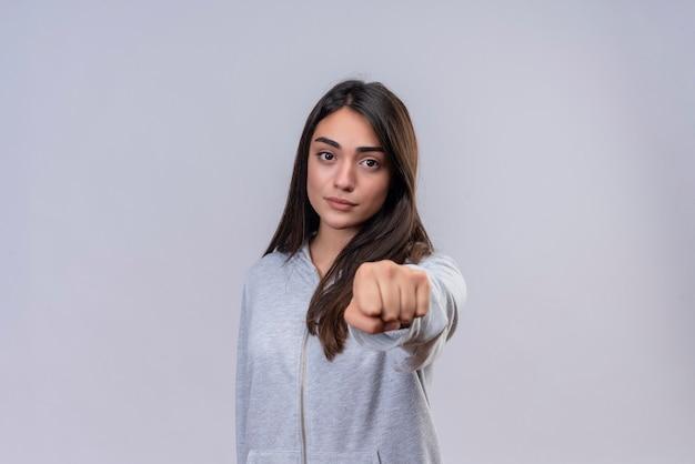 Jeune belle fille à capuche gris regardant la caméra serrant le poing à la caméra avec une expression de colère debout sur fond blanc