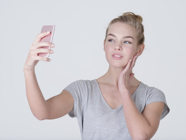 Jeune belle fille caucasienne fait des selfies. heureuse femme merveilleuse avec un téléphone portable en mains