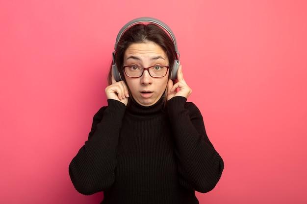 Jeune belle fille dans un col roulé noir et des lunettes avec un casque surpris et confus