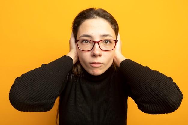 Jeune belle fille dans un col roulé noir et des lunettes d'être confus et inquiet avec les mains sur sa tête
