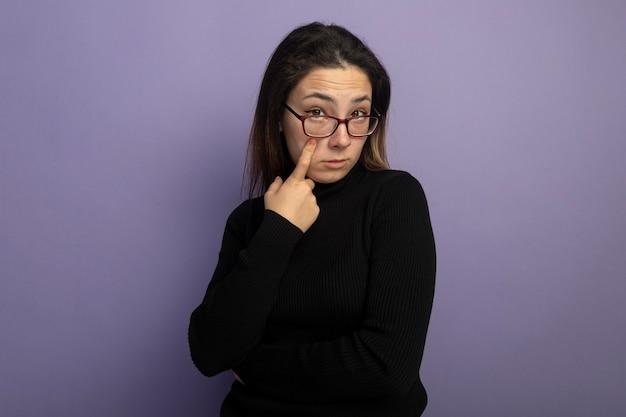 Jeune Belle Fille Dans Un Col Roulé Noir Et Des Lunettes Pointant Avec Le Doigt Sur Son œil étant Sceptique Photo gratuit