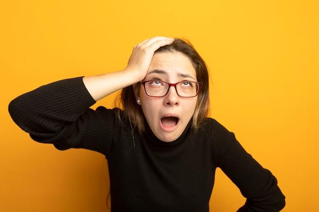 Jeune belle fille dans un col roulé noir et des lunettes à la recherche de confus et inquiet avec la main sur sa tête