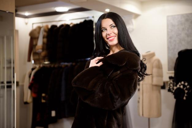 La jeune belle fille dans un manteau de fourrure dans le magasin mesure et choisit des vêtements