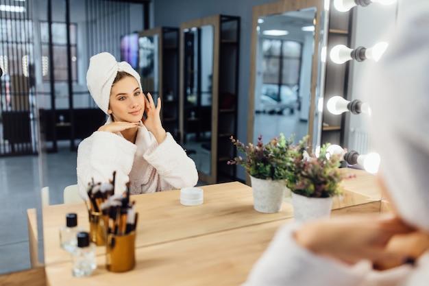 Jeune belle fille dans un peignoir blanc et avec une serviette sur la tête après une douche devant un miroir.