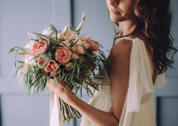 Jeune belle fille dans une robe chic avec un bouquet de fleurs