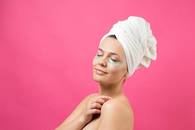 Jeune belle fille dans une serviette blanche sur la tête porte des patchs de gel de collagène sous ses yeux