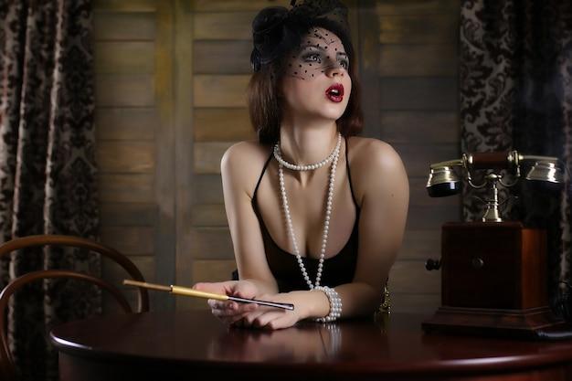 Jeune belle fille dans un style vestimentaire du début des années trente chicago avec un embout buccal