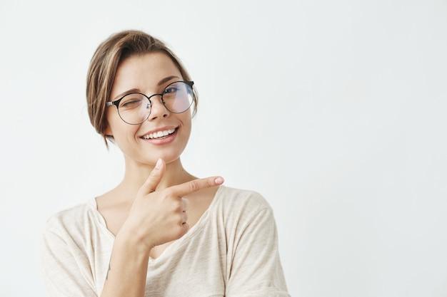 Jeune belle fille dans des verres souriant un doigt pointé clignotant dans le côté.