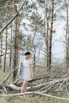 Jeune belle fille dans une veste en jean dans la forêt en été avec des arbres secs 1