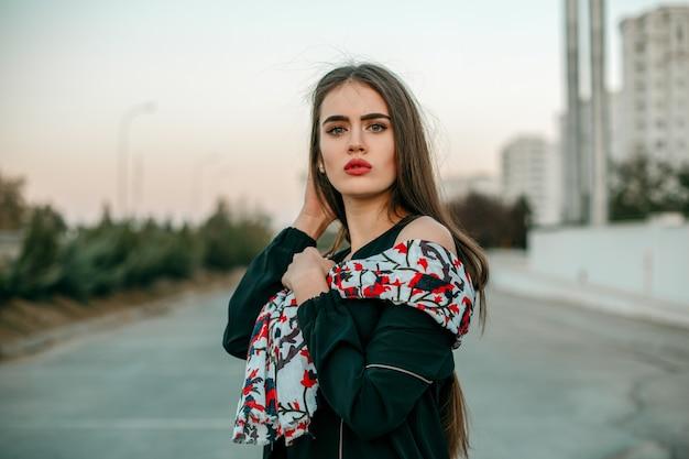 Jeune belle fille dans une veste noire avec une écharpe posant le soir dans la rue.
