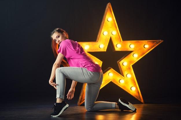 Jeune belle fille danseuse danse hip-hop sur une étoile avec fond de lampe