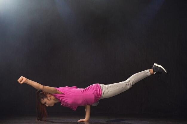 Jeune belle fille danseuse danse hip-hop sur fond noir