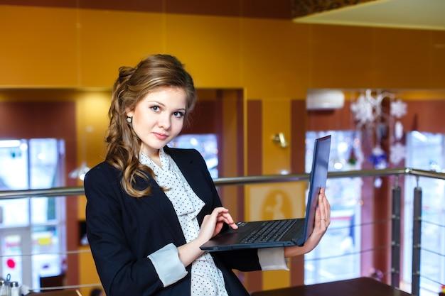 Jeune belle fille debout dans un café et travaillant sur un ordinateur portable
