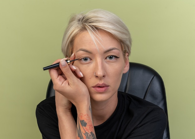 Jeune belle fille dessiner une flèche avec un eye-liner isolé sur un mur vert olive
