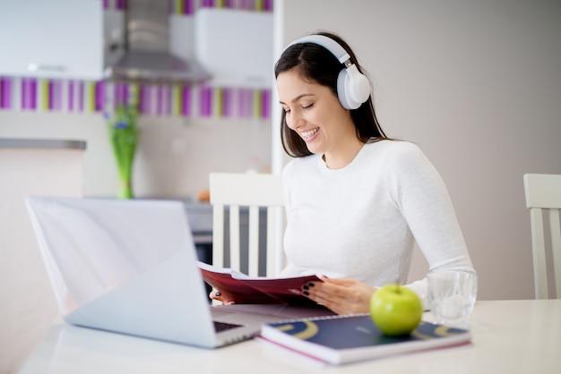 Jeune belle fille détendue est assise à la table de la cuisine avec des écouteurs étudie depuis son ordinateur portable et ses cahiers dans une pièce lumineuse.