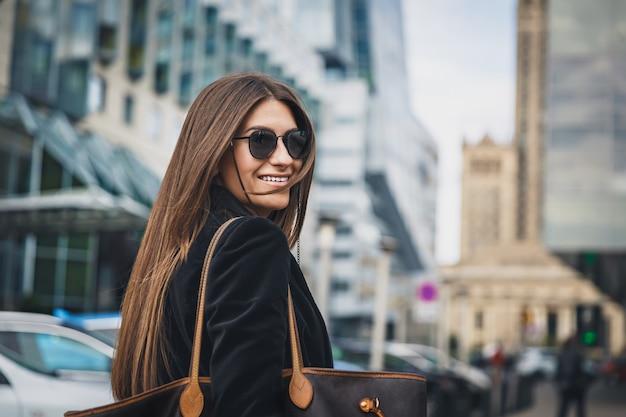 Jeune belle fille élégante à lunettes de soleil marche dans la rue. close up portrait de femme se retourne devant la caméra et sourit.