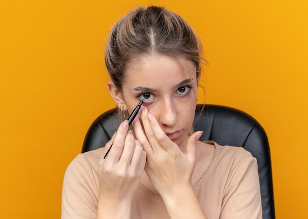 Jeune belle fille est assise à table avec des outils de maquillage dessiner une flèche avec un eye-liner isolé sur un mur orange