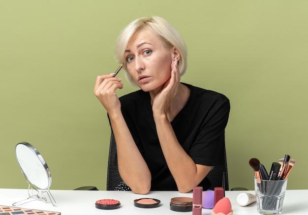 Jeune belle fille est assise à table avec des outils de maquillage dessiner une flèche avec un eye-liner isolé sur un mur vert olive