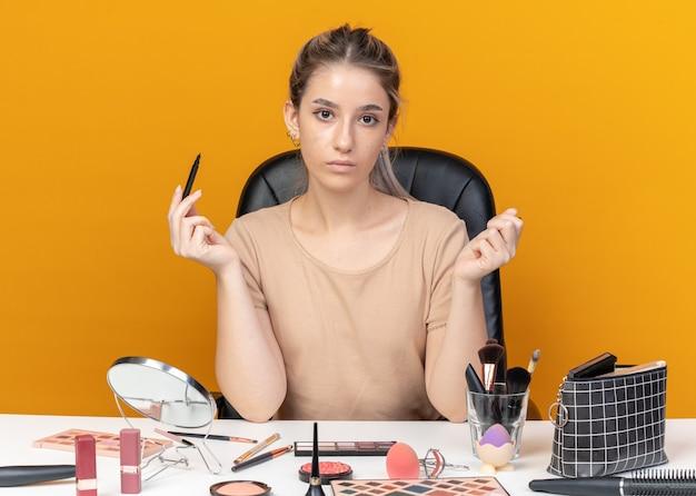 Jeune belle fille est assise à table avec des outils de maquillage tenant un eye-liner isolé sur un mur orange