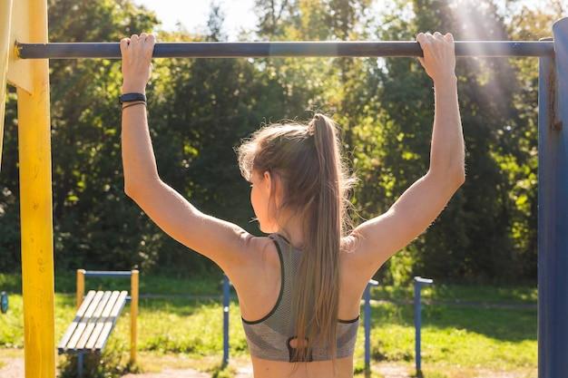 Jeune belle fille faisant des tractions sur le terrain de sport en plein air.