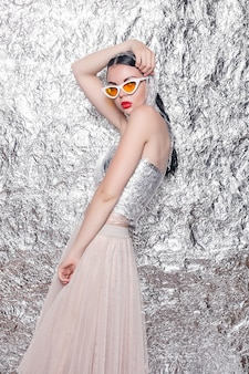 Jeune belle fille sur un fond argenté. femme artistique de style avec maquillage de fantaisie d'art. la créativité. portrait de mode d'une belle jeune fille élégante avec une fête lumineuse
