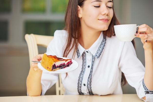 Jeune belle fille heureuse prenant le petit déjeuner café et cheesecake assis à la table