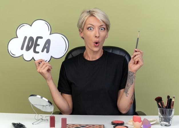 Une jeune belle fille impressionnée est assise à table avec des outils de maquillage tenant une bulle d'idée avec un pinceau de maquillage isolé sur un mur vert olive
