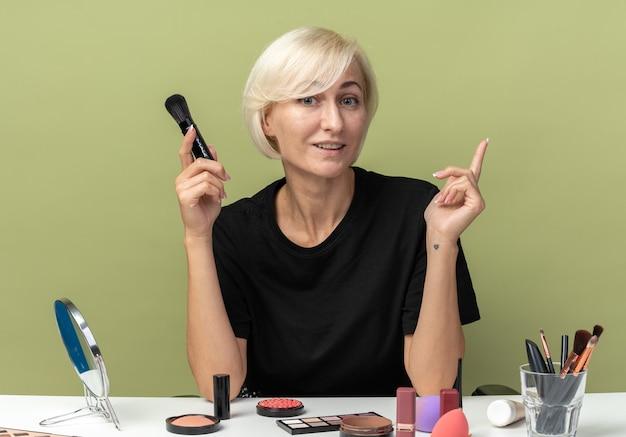 Une jeune belle fille impressionnée est assise à table avec des outils de maquillage tenant des pointes de pinceau à poudre isolées sur un mur vert olive