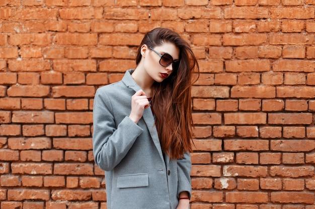 Jeune belle fille avec des lunettes de soleil en manteau gris près du mur de briques rouges