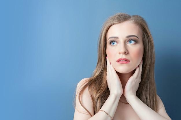 Jeune belle fille avec les mains sur le visage sur un fond bleu, levant les yeux vers la gauche.