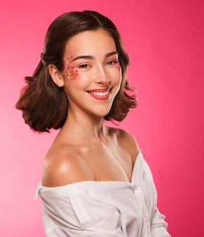 Jeune belle fille avec un maquillage lumineux.