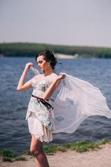 Jeune belle fille marche au bord du lac