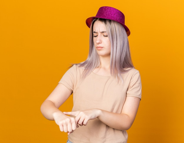 Jeune belle fille mécontente portant un chapeau de fête montrant le geste de l'horloge du poignet